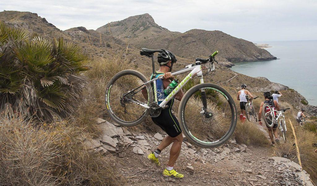 Syklist med sykkel på armen